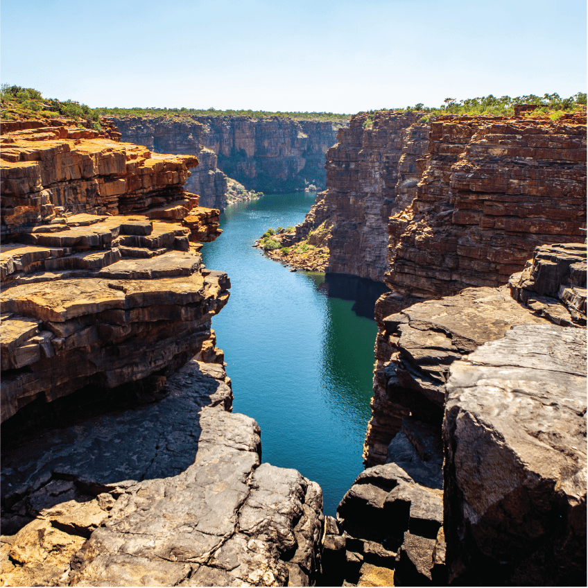 High angel view over King George River Gorge and plateau in the Kimberleys with lush bushes and sandstone formation in the foreground and background